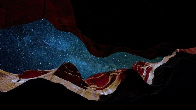Looking up at a star filled sky from inside a canyon
