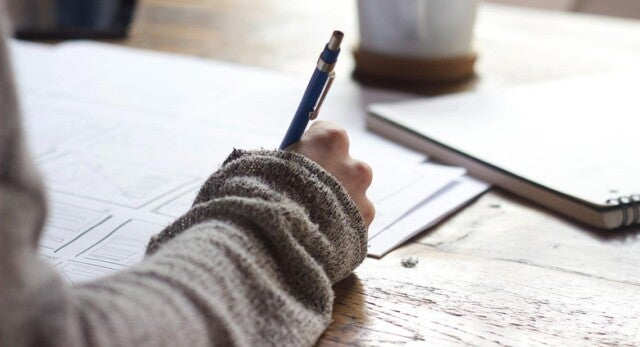 A hand writing with a pen